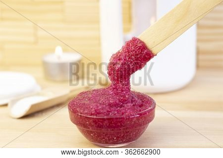 Natural Pink Body Scrub Made From Sugar. Pink Scrub In A Glass Cup On A Background Of Candles And Su