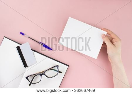 Female Hand Holding White Card Mock-up With Copy Space On Pink Background. Notebook, Sketchbook, Eye