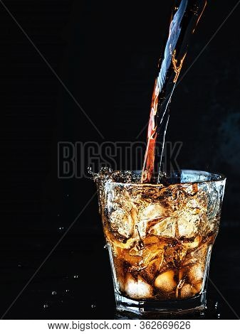 Cool, Soft Carbonated Cola Drink Is Poured Into A Glass Of Ice. Soda Water Refreshing Drink Isolated