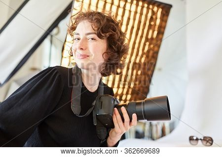 Confident young photographer with SLR camera in the photo studio