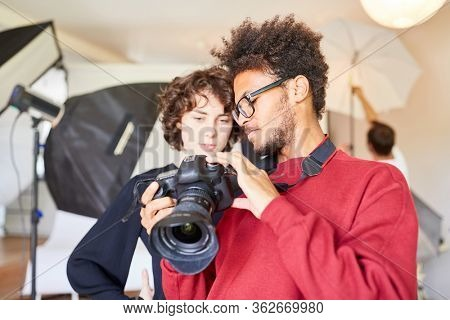 Young photographer explains the SLR camera to his photo assistant