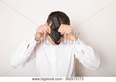 Bankruptcy - Business Person Holding An Empty Wallet. Man Showing  The Inconsistency And Lack Of Mon