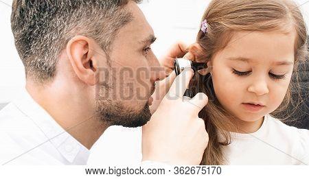Otolaryngologist Checking Childs Ear Using Otoscope. Hearing Exam For Little Girl Close-up. Otitis M