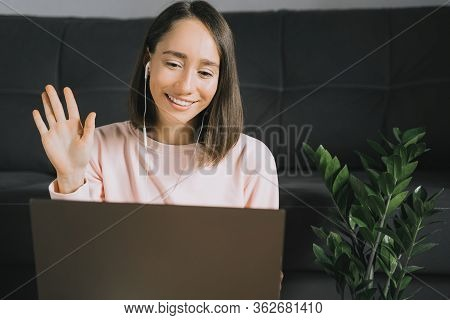 Happy Young Woman Using Laptop, Calling Her Friends Or Family By Video Chat With Headphones And Wavi