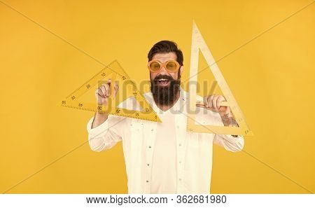 School Of Engineering. Happy Engineer Or Designer. Smart Engineer Holding Triangles On Yellow Backgr
