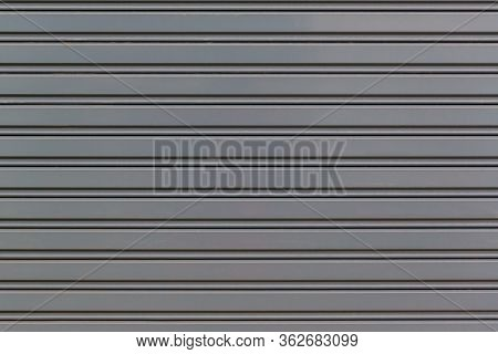 Metallic Roll Up Door. Old Steel Rolling Shutter Background. Metal Security Shutters Protecting A Sm