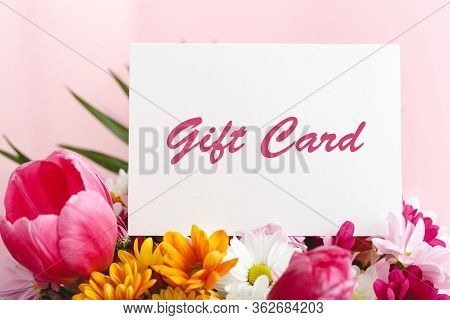 Gift Card In Flowers Bouquet On Pink Background. Gift Card Present Coupon For Woman. Surprise Vouche