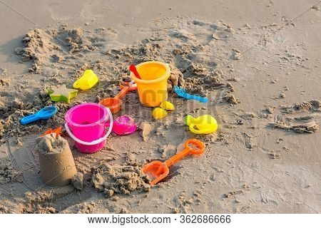 Plastic Sandbox Toys On The Sand. Kids Toys On Tropical Sand Beach. Plastic Shovel And Sea Animal Mo
