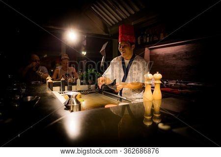 May, 2018 - Ari Atoll, Maldives: Happy Teppanyaki Chef Cooking Vegetables At Teppan In A Japanese St