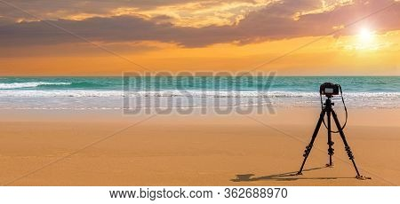 Digital Professional Camera Stand On Tripod Photographing Sea. Twilight Sky Background. Colorful Sun
