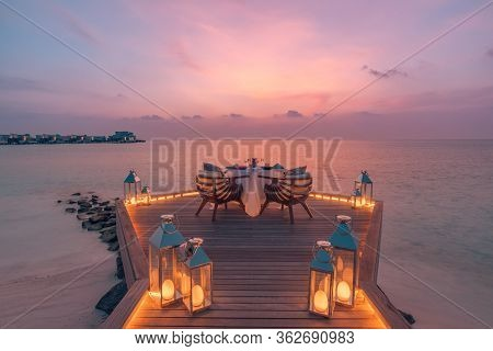 Romantic Couple Dinner Background With Candle Lamps And Sea View Sand Beach, Sunset Sky. Honeymoon A