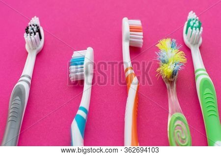 Multicolored New Toothbrushes And An Old Toothbrush On A Pink Background. Close Up.the Concept Of De