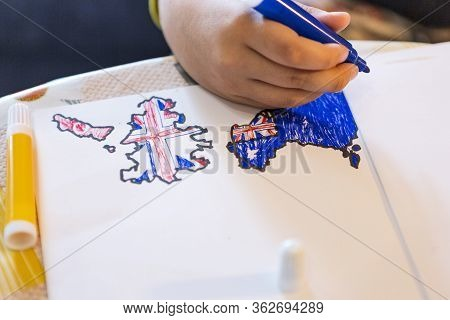 Child Draws Flags On White Sheet At Home. Natural Light. Boy Draws Flags Of Countries. Great Britain