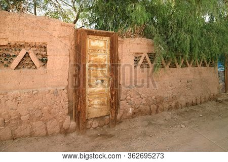 Brown Adobe Outer Wall With Wooden Door And Green Foliage In A Town Of Northern Chile