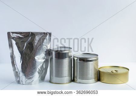 Metal Cans Of Different Sizes, Metallized Flexible Packet On A White Background. A Variety Of Packag