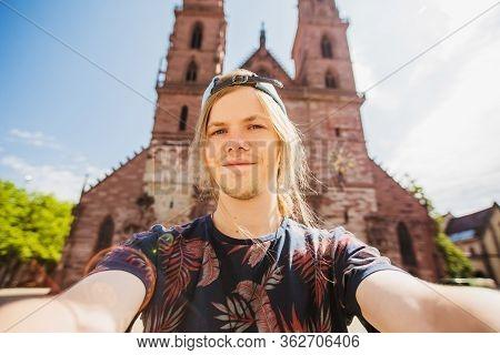 Stylish Happy Man Taking Selfie On Basel Cathedral Background. Happy Tourist In Switzerland. Travel