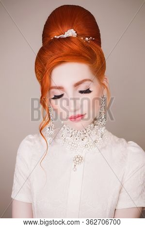 Beauty Portrait. Beautiful Redhead Woman With Retro Hairstyle And Make-up On Gray Background. Beauty