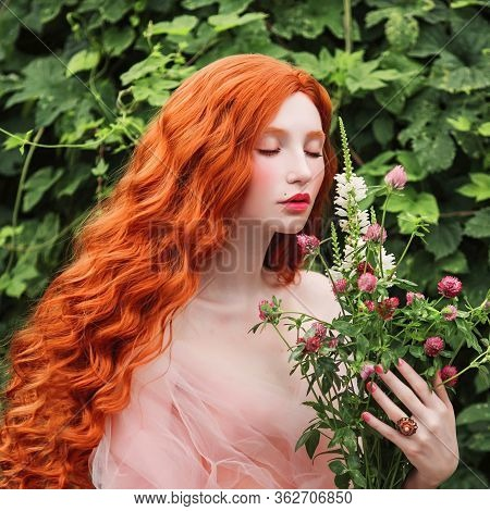 Beauty Portrait. Beautiful Fairytale Girl With Curly Red Hair With A Flying Tulle Dress On The Backg