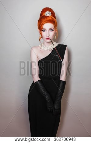 Redhead Retro Girl With A Long Mouthpiece In Her Mouth In A Black Dress And Long Gloves On A Gray Ba