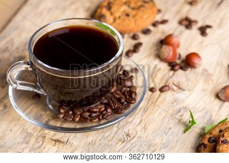 Black Coffee In A Glass Cup With Coffee Beans. Near Cookies And Hazelnuts