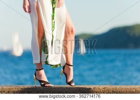 Woman Legs Wearing Fashionable Dress And High Heels Summer Shoes. Female Walking On Sea Coast. Yacht