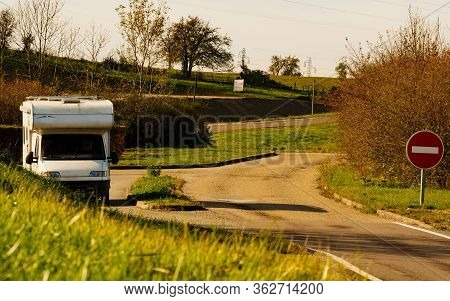 Camper Car Recreational Vehicle With Alcove Parking On Roadside. Holidays And Travel In Motor Home.