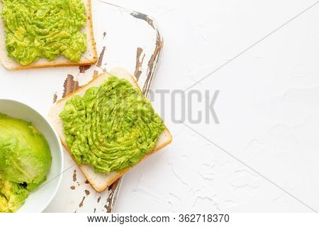 Homemade Avocado Toasts And Smashed Fresh Ripe Avocados In Bowl On Wooden Rustic Cutting Board On Wh