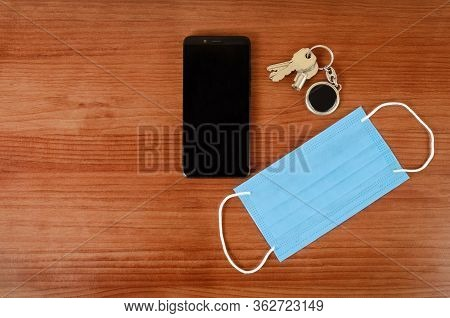 Keys, Medical Mask And Smartphone On A Table. Top View