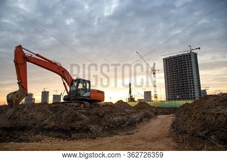 Red Excavator During Groundwork On Construction Site. Hydraulic Backhoe On Earthworks. Heavy Equipme