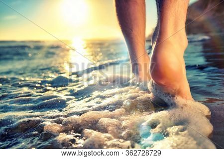 Enjoying A Barefooted Walk At The Ocean