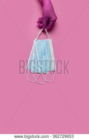 Doctor Holds Respiratory Surgical Face Mask In Hands Pink Medical Gloves On Pink Background. Pandemi