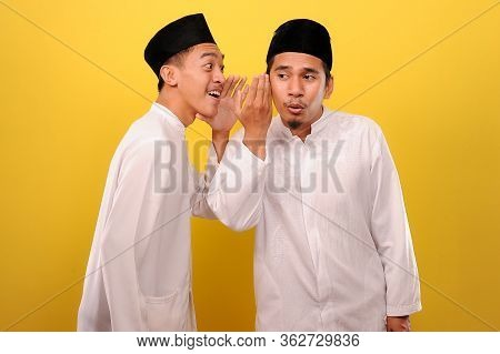 Image Of Two Young Asian Muslim Men In Muslim Cloth, Whispering Secrets Or Gossips To Each Other. In