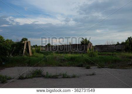 Abandoned Concrete Silage Storage Facility. Evening Landscape. Abandoned Farm Buildings.