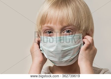 Fair Haired Boy Wears Sterile Medical Mask. Child Wearing Mask Protection Against Flu.