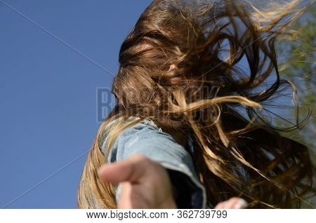 Portrait Girl Hair In The Wind Hiding The Face, Giving A Hand, On Blue Sky