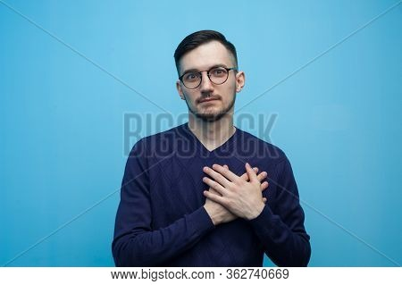 Positive Kind Young Man In Glasses Put His Hands To His Heart. Concept Of Sincerity And Kindness. Ad