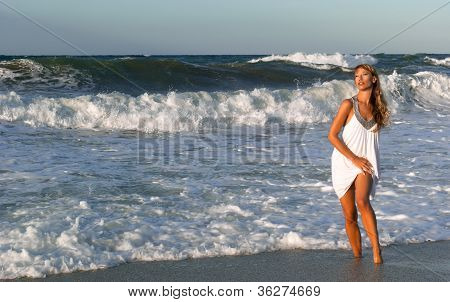 Woman In White Dress Posing On The Sea Coast