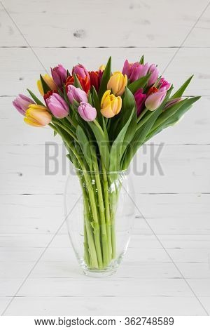 Glass Vase With Fresh Multi-colored Tulips. Located On A Wooden White Background.
