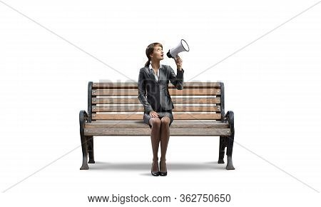 Young Woman With Megaphone On Wooden Bench. Beautiful Girl In Business Suit Sitting On Bench. Pretty