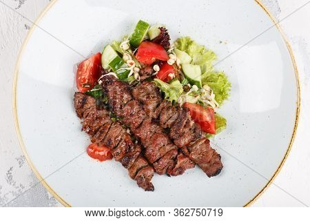Beef Skewers Served On A Plate With Vegetable Salad.