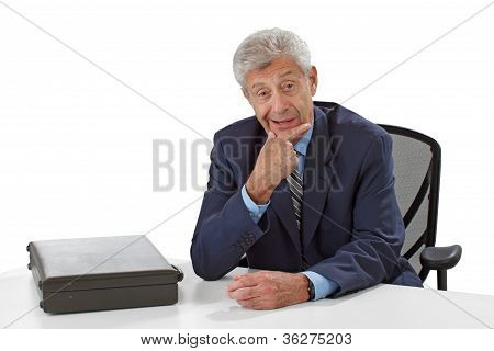 Attentive Friendly Senior Business Man Listens Stroking His Chin
