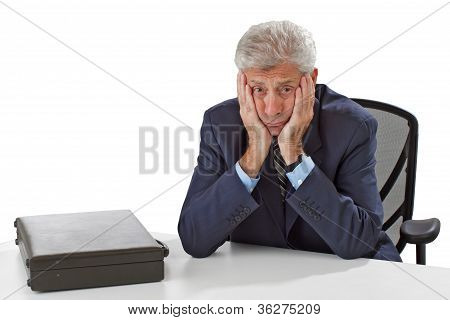 Worried Senior Business Man Rests Chin On Both Hands