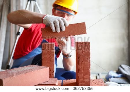 Close-up Of Professional Builder Repairing House. Professional Constructor Laying Bricks. Man In Spe