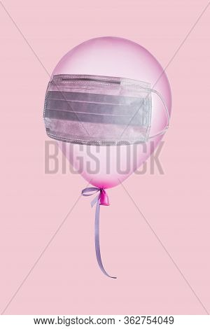 Pink Balloon With Medical Mask On It Hanging On Air On Pink Wall. Protection Against Virus Or Flu. B