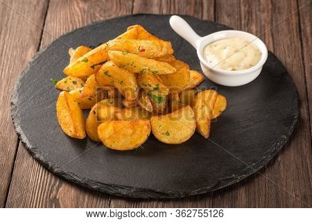 Fried Potato Wedges On A Round Black Board With Mustard Sauce.
