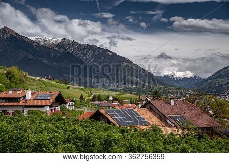Panorama Of Solar Batteries On Roof Top, Green Slopes Of The Mountains Of Italy, Trentino, Dolomites