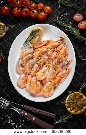 Boiled King Prawns On A White Plate. Decoration With A Slice Of Lemon And A Branch Of Rosemary.