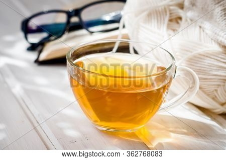 Cup Of Tea, Open Book And Eyeglasses  With Sumlight Shadow On White Wooden Table. Cozy Morning At Ho
