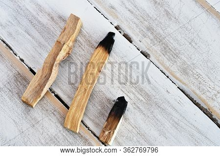 A Top View Image Of Three Palo Santo Smudge Sticks On A White Wooden Background.