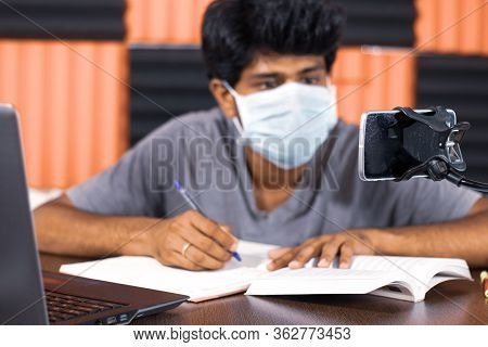 Young Man With Medical Mask E-learning At Home Due To Covid-19 Or Coronavirus Isolation Concept - Co